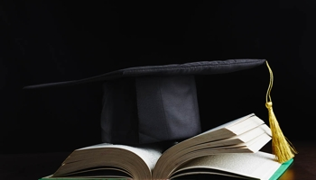 Graduation mortarboard on an open book
